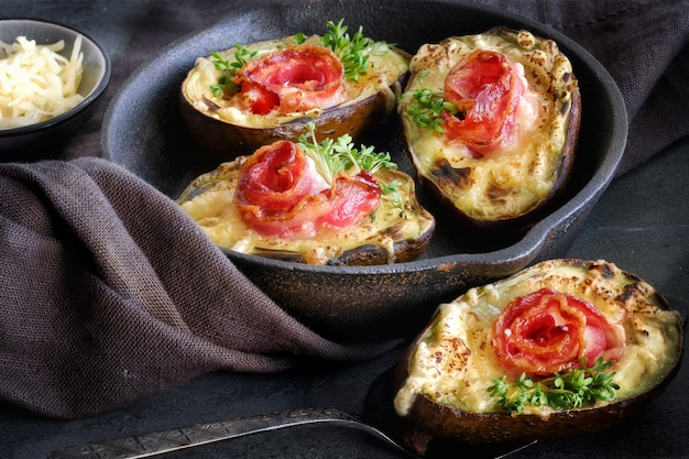 Piatto dietetico keto: barche di avocado con pancetta croccante, formaggio fuso e germogli di crescione sul buio