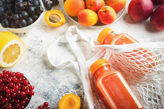 Piatto disteso, bacche, frutta, succo in bottiglia e borsa a rete su uno sfondo grigio.