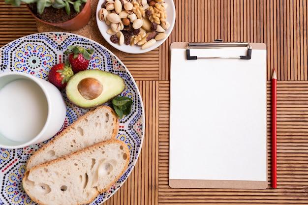 Piatto disteso cibo sano e blocco note