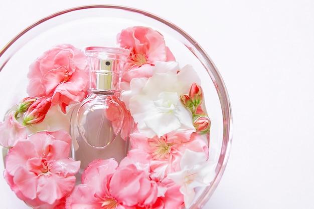 Piatto disteso con bottiglia di profumo delicato in lastra di vetro con fiori. vasca da bagno e spa piatta. spazio copia modello. profumeria, cosmetici, accessori femminili, collezione di fragranze