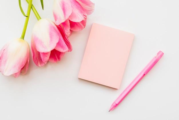 Piatto disteso con bouquet di fiori e notebook con penna