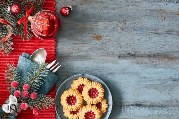 Piatto disteso con decorazioni natalizie in verde e rosso con bacche glassate e bigiotteria e biscotti di natale