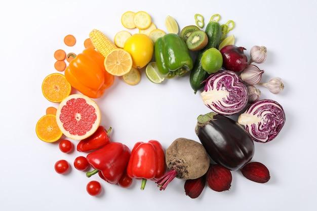 Piatto disteso con diverse verdure e frutta su bianco