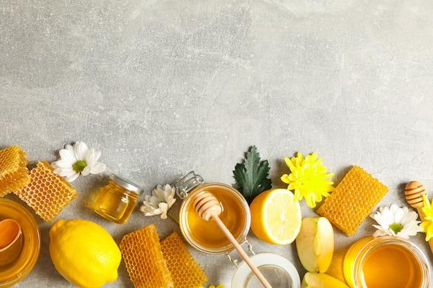 Piatto disteso con miele, fiori e frutti su grigio