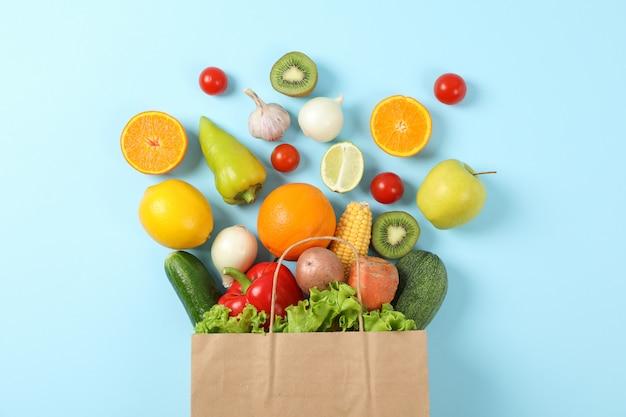 Piatto disteso con sacchetto di carta, frutta e verdura su blu