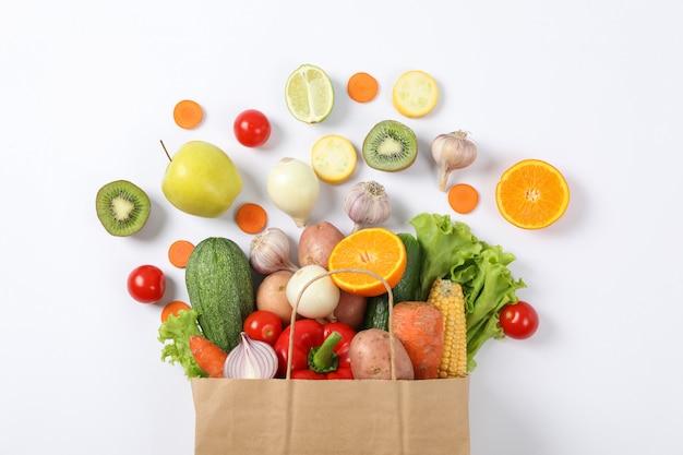Piatto disteso con sacchetto di carta, verdure e frutta su bianco
