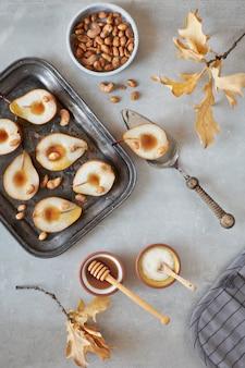 Piatto disteso con un vassoio di pere al forno con noci caramellate
