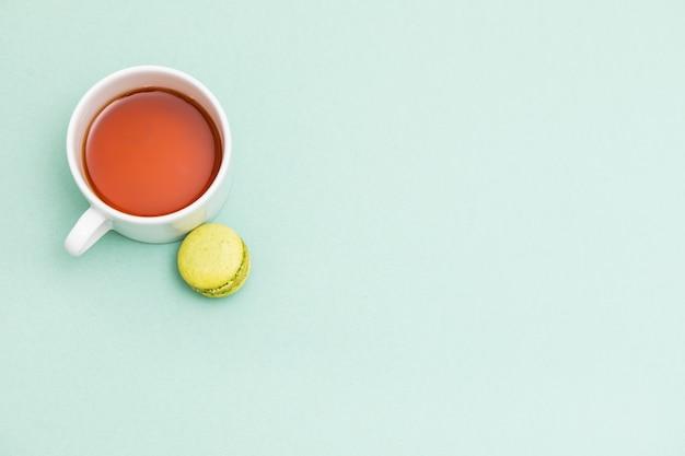 Piatto disteso con una tazza di tè del mattino e macarons. vista dall'alto, copyspace.