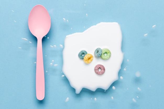 Piatto disteso cucchiaio rosa e spruzzi di latte con cereali