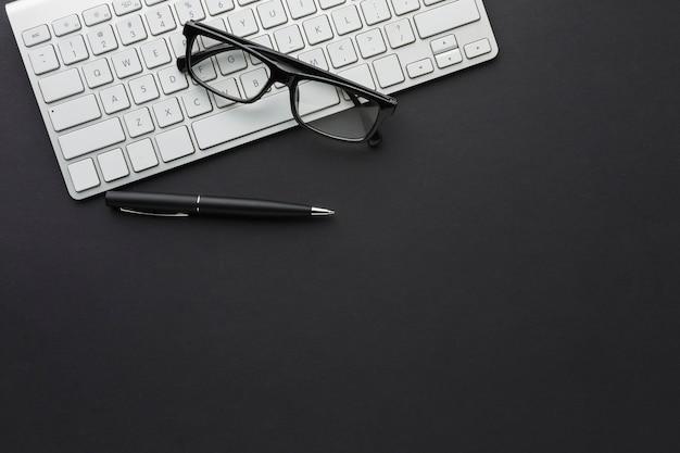 Piatto disteso del desktop con occhiali e tastiera
