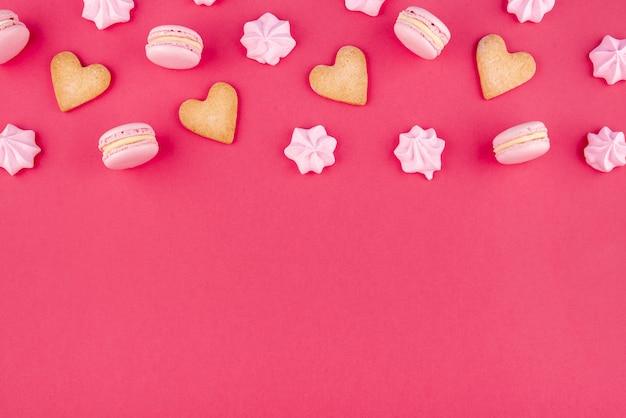 Piatto disteso di biscotti a forma di cuore con macarons e meringa