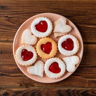Piatto disteso di biscotti a forma di cuore con marmellata