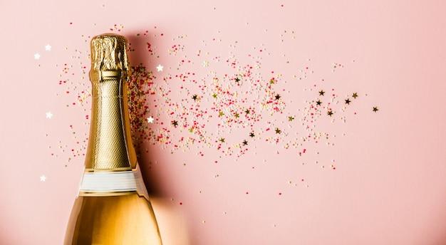 Piatto disteso di celebrazione. la bottiglia di champagne con spruzza su fondo rosa.