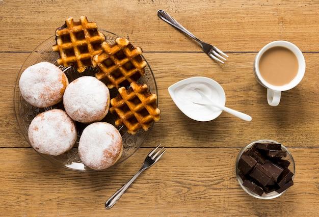 Piatto disteso di cialde e ciambelle con caffè e cioccolato