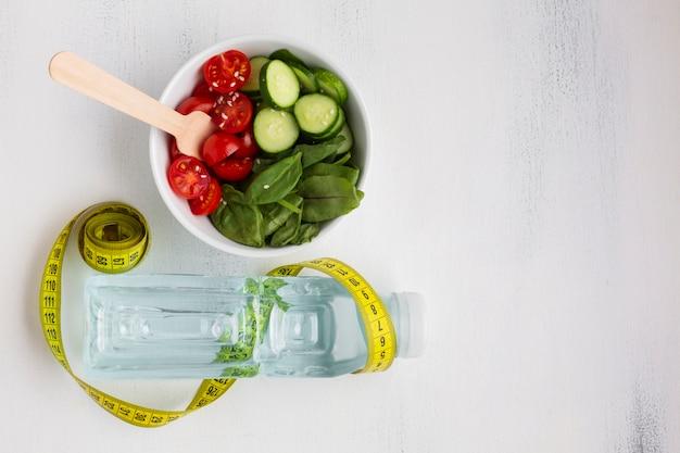 Piatto disteso di ciotola di insalata e bottiglia d'acqua