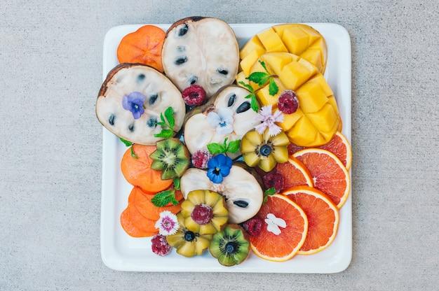 Piatto disteso di frutti tropicali esotici. kiwi d'oro, cachi, lampone, mango, arance e menta.