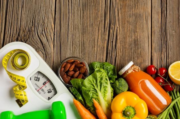 Piatto disteso di generi alimentari e scala sul tavolo di legno