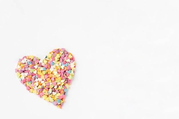 Piatto disteso di granelli colorati a forma di cuore