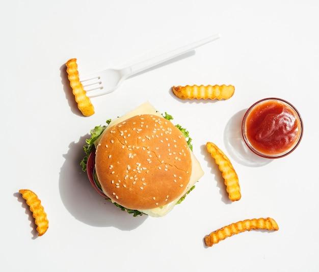 Piatto disteso di hamburger con patatine fritte e ketchup
