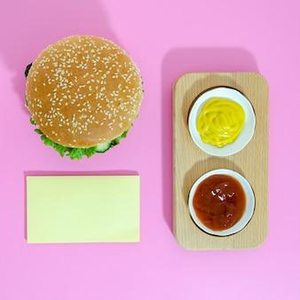 Piatto disteso di hamburger con senape e ketchup