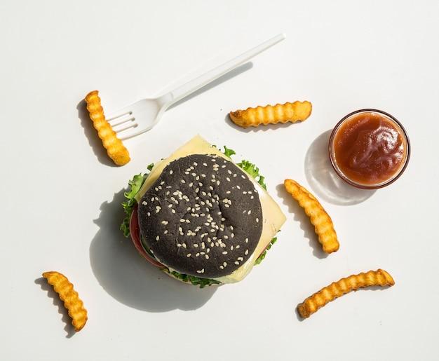 Piatto disteso di hamburger nero con patatine fritte
