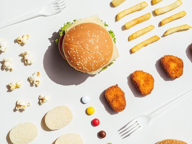 Piatto disteso di hamburger, patatine fritte, pepite e patatine