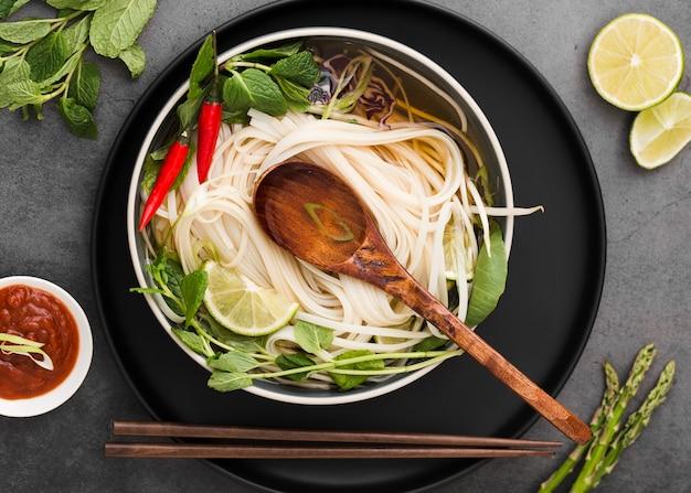 Piatto disteso di noodles in una ciotola con cucchiaio e salsa