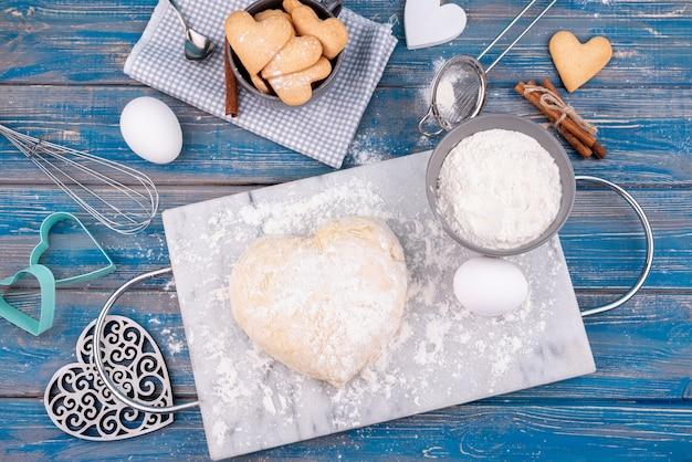 Piatto disteso di pasta a forma di cuore con biscotti di san valentino
