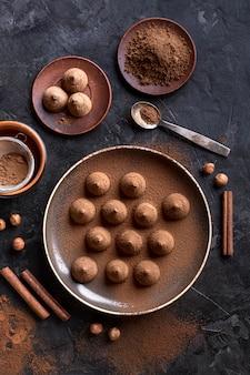 Piatto disteso di piastra con caramelle al cioccolato e bastoncini di cannella