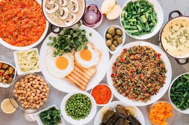 Piatto disteso di piatti con olive e uova fritte