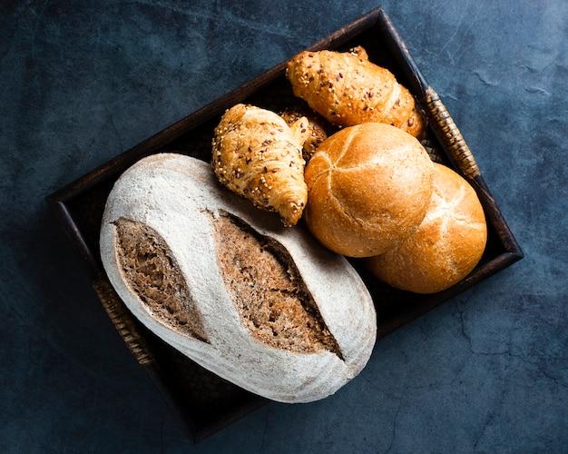Piatto disteso di un cesto con pane e cornetti
