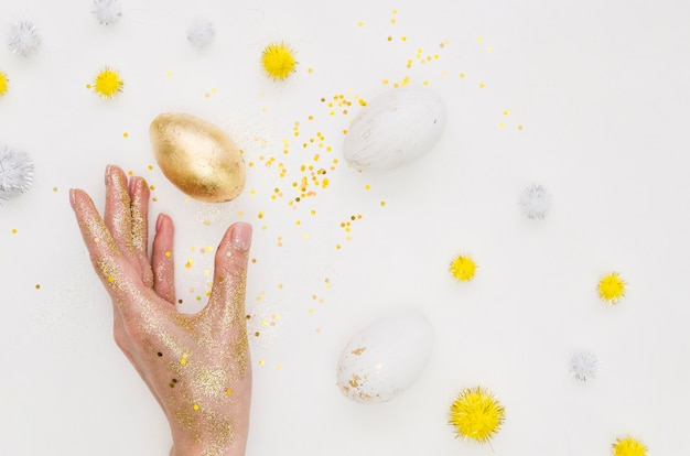 Piatto disteso di uovo d'oro per pasqua con glitter e denti di leone