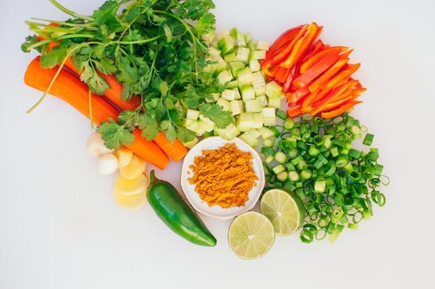 Piatto disteso di verdure fresche tagliate. carota sana, cipolla verde, prezzemolo, lime, aglio, jalapeno su sfondo bianco. mix di verdure per vegani. concetto di cibo.