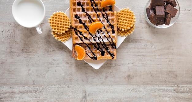 Piatto disteso di waffle con latte e cioccolato