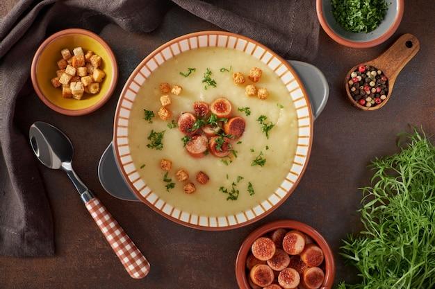 Piatto disteso di zuppa di crema di patate con crostini e salsiccia