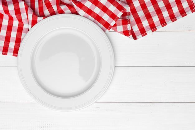 Piatto e asciugamano vuoti sopra la tavola di superficie di legno