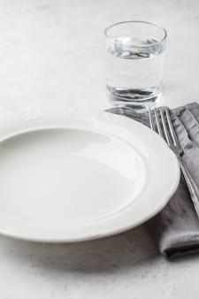 Piatto e bicchiere d'acqua vuoti, fondo bianco. concetto di digiuno medico.