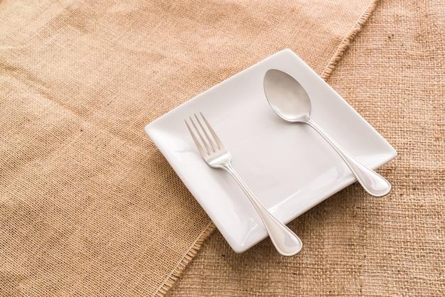 Piatto e cucchiaio bianchi vuoti, forcella