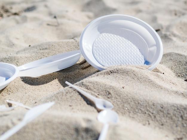 Piatto e cucchiaio di plastica sulla sabbia della spiaggia