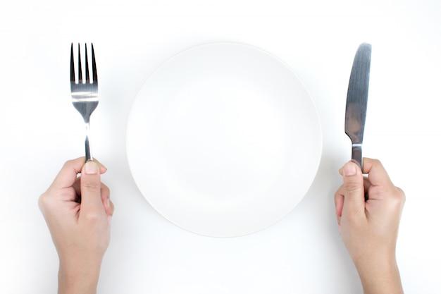 Piatto e cucchiaio nella vista superiore, fondo bianco isolato.