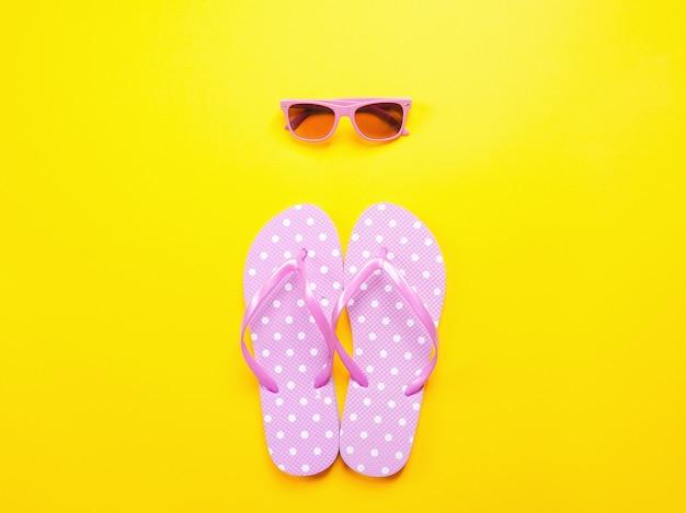 Piatto estivo. flip-flop e occhiali da sole rosa degli accessori della spiaggia su fondo giallo.