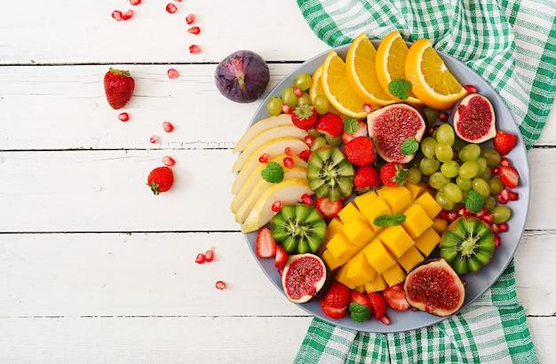 Piatto frutta e bacche. mango, kiwi, fichi, fragole, uva, pera e arancia.