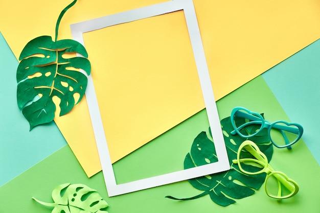 Piatto geometrico con cornice in carta, foglie di monstera esotiche e occhiali da sole a forma di cuore