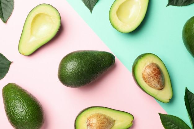 Piatto giaceva con avocado e foglie su uno sfondo di due toni, vista dall'alto