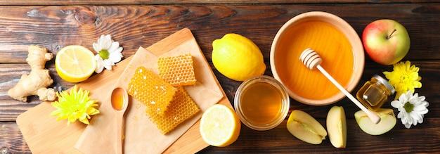 Piatto giaceva con miele, fiori e frutti su fondo di legno