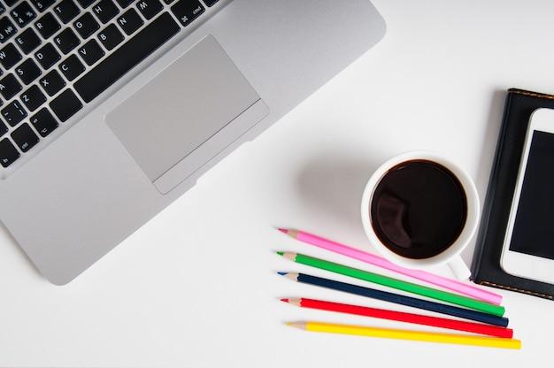 Piatto giaceva su area di lavoro in legno bianco con computer portatile, gadget cellulare, forniture e caffè nero.