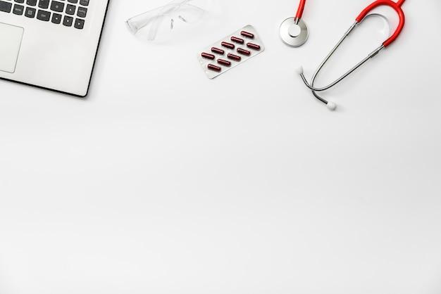 Piatto giaceva su sfondo bianco, antidolorifici con bicchiere d'acqua prescritto da un medico, copia spazio.