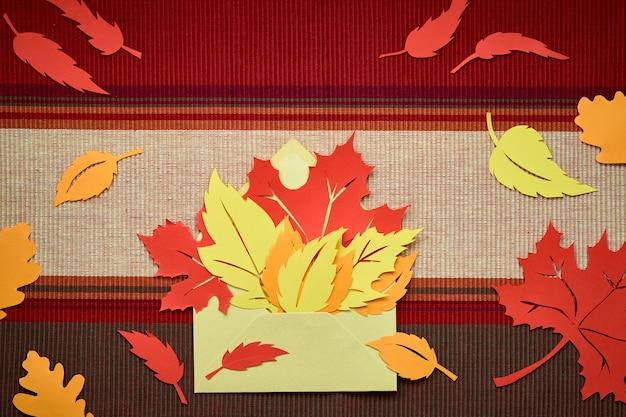 Piatto giaceva sul buio con foglie di carta rossa e arancione in busta
