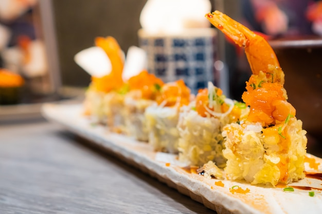 Piatto giapponese, croccante rotolo di tempura di gamberi servito su un piatto rettangolare posto sul tavolo di legno