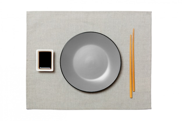 Piatto grigio rotondo vuoto con le bacchette per sushi e salsa di soia sul tovagliolo grigio